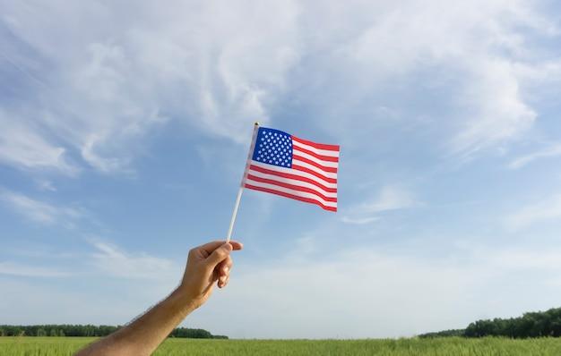 Usa-flagge in der hand. festliche usa-flagge in der hand gegen blauen himmel und sommerlandschaft. amerikanisches feiertagskonzept. foto in hoher qualität