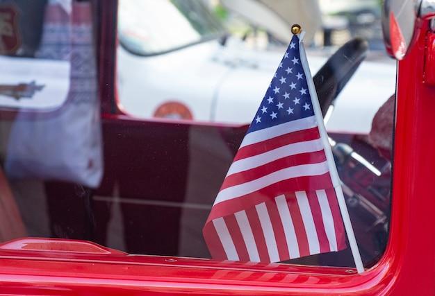 Usa-flagge klein im roten auto hinter glas