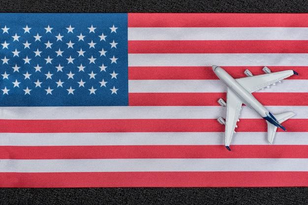 Usa flagge mit spielzeugflugzeug. flüge nach vereinigte staaten von amerika. wiederaufnahme der flüge nach quarantäne