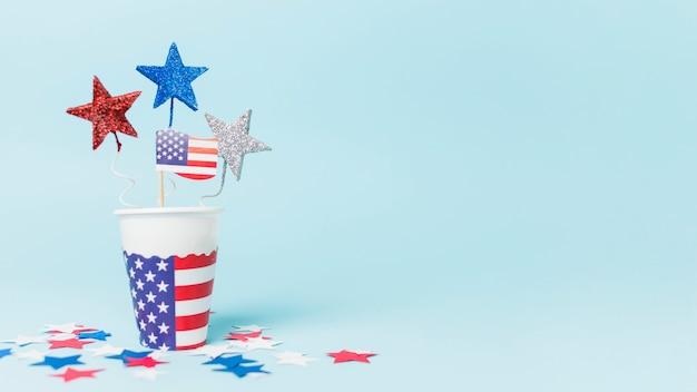 Usa-flaggen- und -sternstützen in der wegwerfschale gegen blauen hintergrund