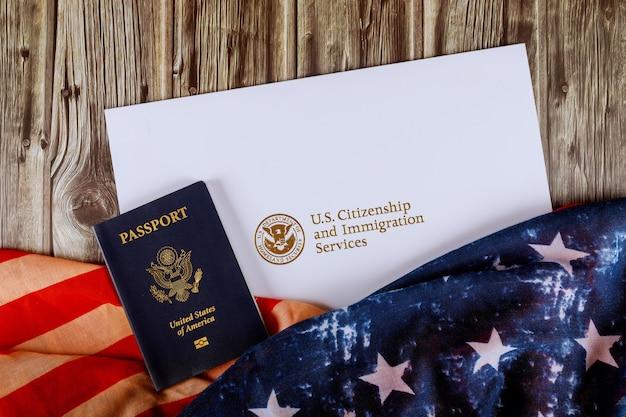 Usa-pass und einbürgerungsurkunde der staatsbürgerschaft us-flagge über holztisch