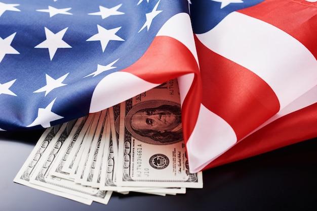 Usa-staatsflagge und währung usd geldbanknoten auf einer dunkelheit. geschäft und finanzen