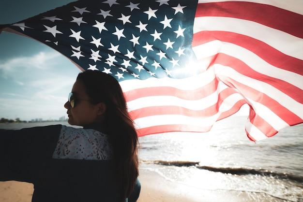 Usa-unabhängigkeitstag, 4. juli. frau, die flagge der vereinigten staaten von amerika auf strand hält.