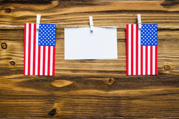 Usa-unabhängigkeitstaghintergrund auf wäscheleine mit leerer karte