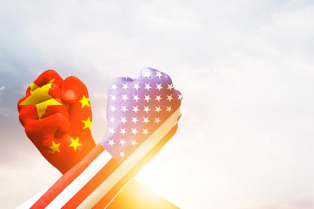 Usa- und china-flaggendruckschirm auf armdrücken mit himmel. vereinigte staaten von amerika gegen china-handelskrieg bestreitet konzept.