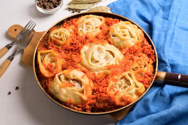 Usbekische manti zu hause in einer pfanne mit gedünstetem gemüse, zutaten - fleisch, gemüse, teig. draufsicht auf einem hellen hintergrund.
