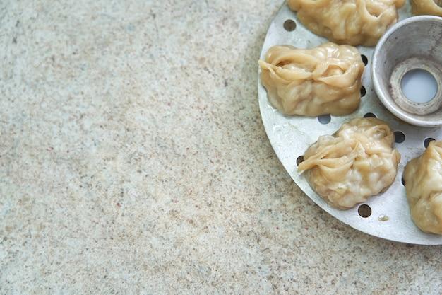Usbekischer nationaler nahrungsmittelmanta, wie mehlklöße, in einem dampfer, gedämpftes lebensmittel. mit freiem text platz. kopieren sie platz