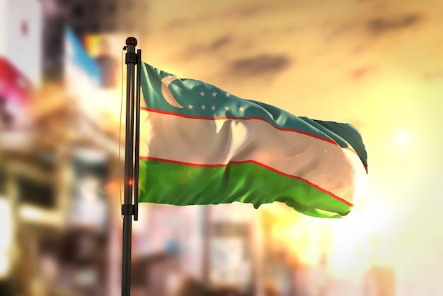 Usbekistan-flagge gegen stadt verschwommener hintergrund bei sonnenaufgang-hintergrundbeleuchtung