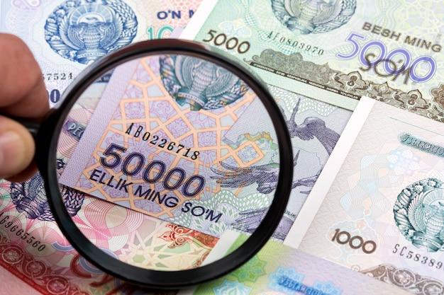 Usbekistisches geld in einer lupe ein geschäftshintergrund