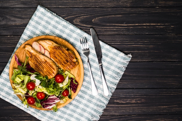 Utensilien in der nähe von gebratenem hähnchen und salat