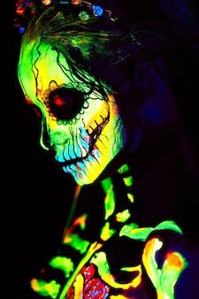 Uv-körperkunstmalerei des weiblichen halloween-skeletts