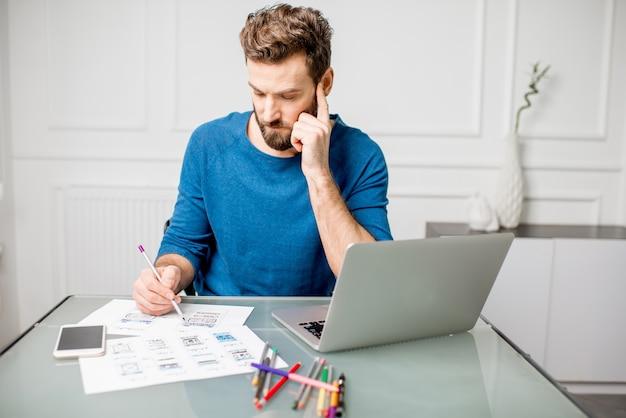 Ux-designer, der an der mobilen anwendung arbeitet, zeichnen im büro zeichnungen skizzieren