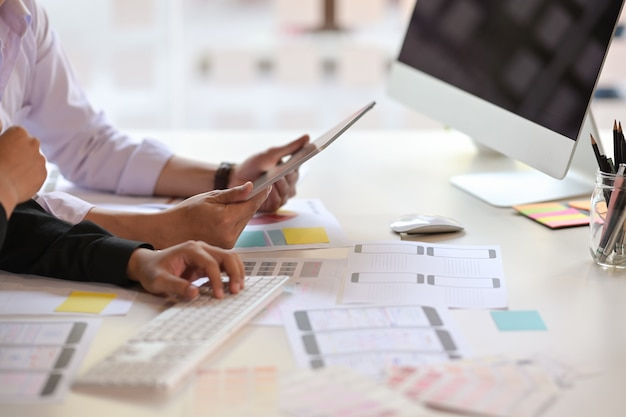 Ux-designerteam unter verwendung der tablette, die wireframe-netz-handyplan entwirft