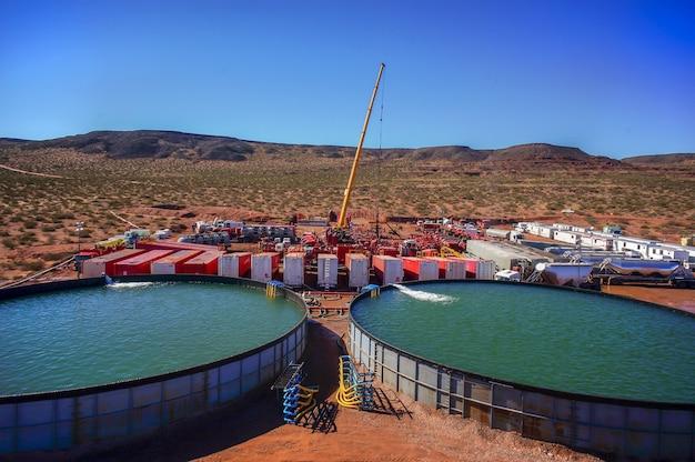 Vaca muerta, argentinien, 26. august 2014: gewinnung von unkonventionellem öl. batterie von pumpwagen für das hydrofracking (fracking).