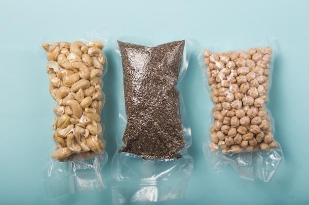 Vakuum-plastiktüte mit cashewnüssen, chiasamen, kichererbsen, isoliert auf blau