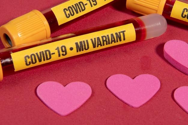 Vakuumröhrchen mit blutprobe für covid-19 mu-variantentest auf rotem hintergrund