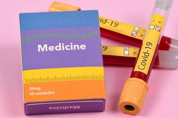 Vakuumröhrchen zur blutentnahme mit krankheitsetikett und medikamentenbox