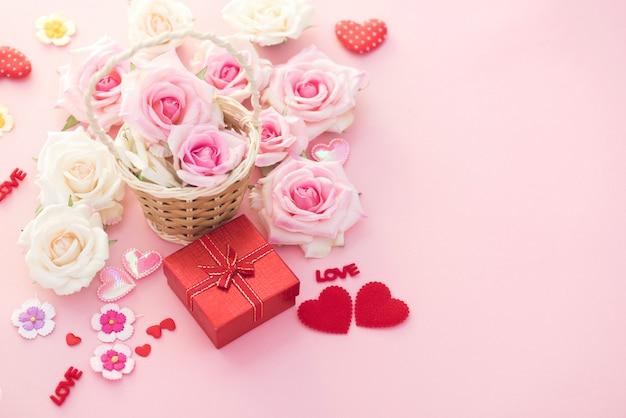 Valentine day-geschenkbox mit roten herzen und rosen auf rosa hintergrund