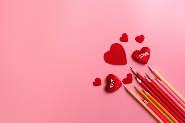 Valentine day-konzept, rote herzen und farbbleistift auf rosa hintergrund