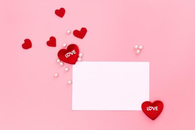Valentine day-konzept, rote herzen und weiße anmerkung über rosa hintergrund