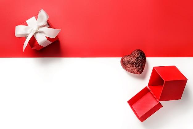 Valentine flach lag. geschenkboxen und ein herz auf rot und weiß mit kopierraum. Premium Fotos