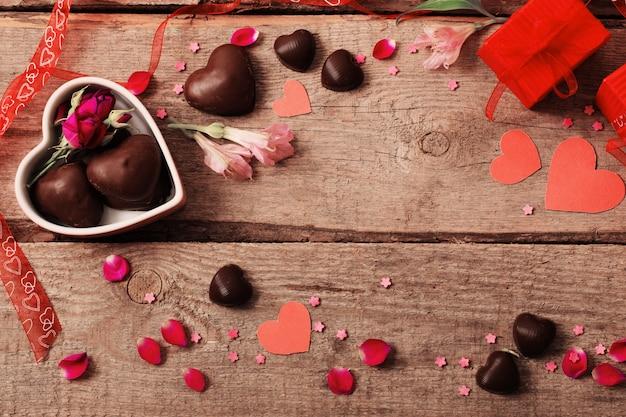 Valentine geschenkbox und rote herzformen auf holzbrett