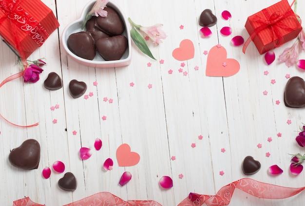 Valentine geschenkbox und rote herzformen auf weißem holzbrett