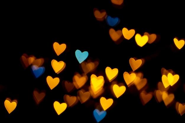Valentine grunge herzförmige lichter hintergrund. gelbgold und blau herzförmig auf schwarzem hintergrund bunte beleuchtung bokeh für die dekoration valentinstag, liebesbilder hintergrund