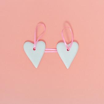 Valentine gruß konzept. reizendes weißes herz zwei, das am rosa band auf papierhintergrund des pastellrosas hängt.