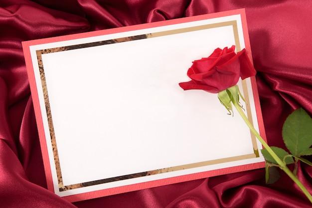 Valentine-karte mit rose auf rotem satin hintergrund