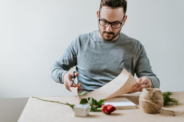 Valentine-konzept. gut aussehender mann, der geschenke für mädchen oder frau einwickelt. geschenkpapier schneiden.