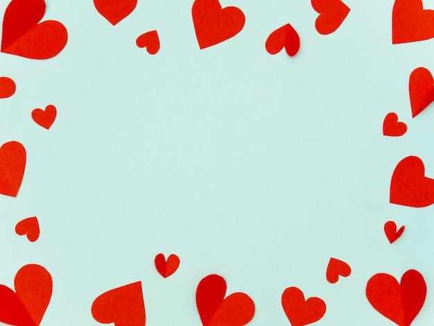 Valentine rahmen machte rotes herzpapier auf cyanfarbenem hintergrund mit copyspace für konzept der liebe.