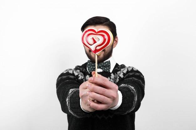 Valentine romantischen mann in schwarzen pullover halten süßigkeiten herzen