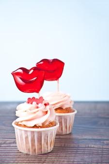 Valentines cupcakes frischkäse-zuckerguss verziert mit lippenförmigen bonbonlutschern