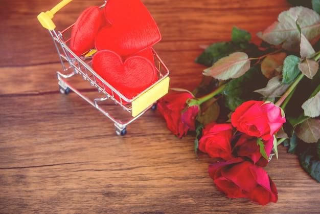 Valentines day shopping rotes herz auf warenkorb liebe konzept shopping-urlaub für liebe valentinstag rote rosen blume auf holz