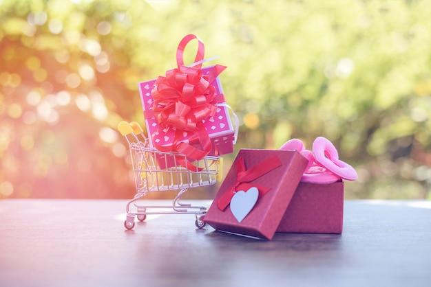 Valentines day shopping und geschenkbox online-shopping valentines day-konzept rosa geschenkbox mit roter schleife am warenkorb