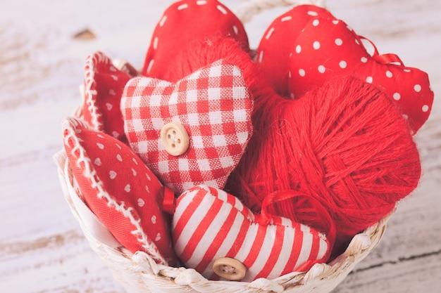Valentinsdekoration: rote textilherzen im weißen korb auf dem schäbigen tisch