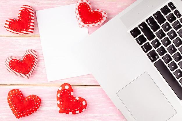 Valentinsgruß-desktop mit rotem handgemachtem genähtem herz-geschenk und laptop