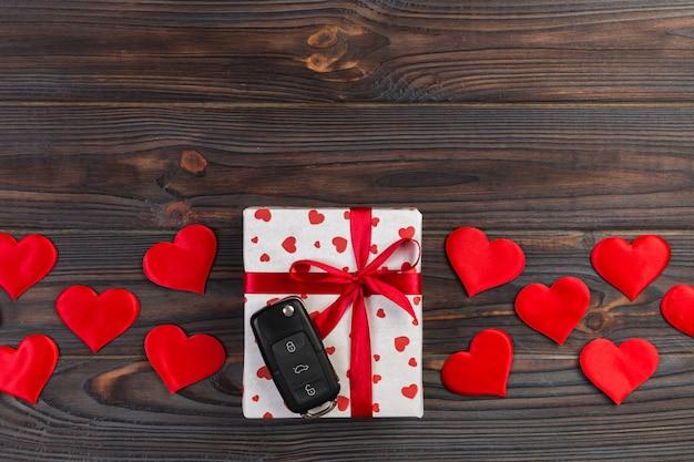 Valentinsgruß oder anderes handgemachtes geschenk des feiertags im papier mit roten herzen, autoschlüsseln und geschenkkasten in der feiertagsverpackung