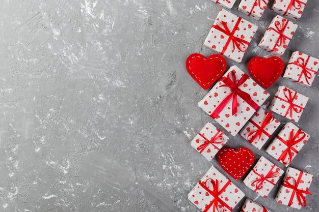 Valentinsgruß oder anderes handgemachtes geschenk des feiertags im papier mit roten herzen und geschenkkasten in der feiertagsverpackung.