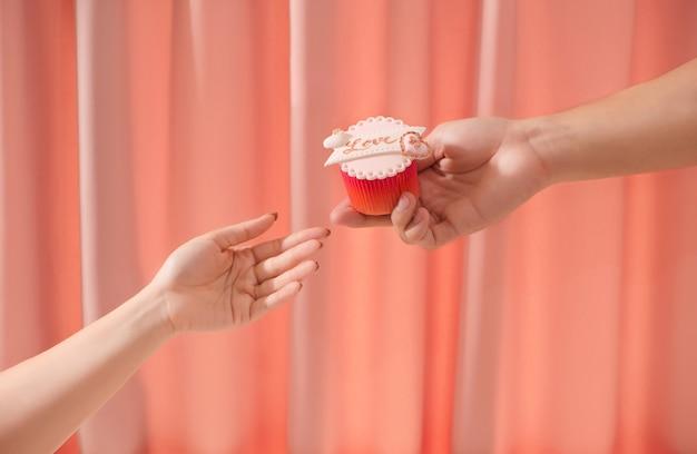Valentinsgruß süßer liebescupcake in der hand auf hellem hintergrund