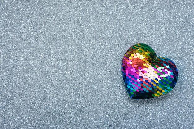 Valentinsgruß-tageshintergrund, modell mit einem lgbt-regenbogenherzen auf silbernem glänzendem funkelnhintergrund. valentine day, liebe, romantik, datierungskonzept, kopienraum