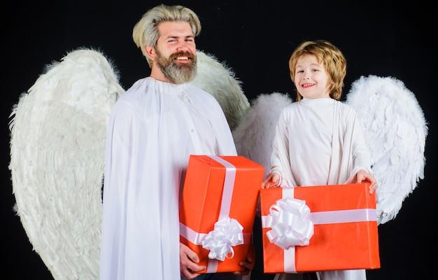 Valentinsgrußengel mit geschenkbox. glücklicher vater mit kleinem sohn im engelskostüm mit geschenk.