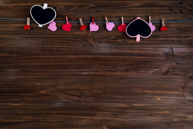 Valentinsgrußherz-kreidebrett mit roten herzen auf braunem hölzernem hintergrund