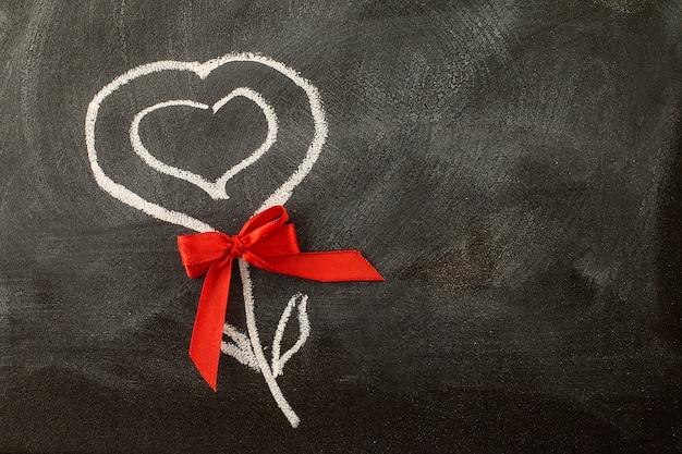 Valentinsgrußherz und roter bogen auf der tafel