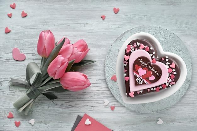 Valentinsgrußherzkuchen mit schokolade, zuckerdekorationen und text
