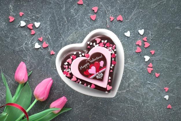 Valentinsgrußherzkuchen mit schokoladen- und zuckerdekorationen