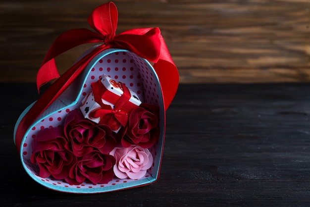 Valentinsgrußhintergrund mit roten herzen und stieg in geschenkbox auf dunklem hölzernem hintergrund