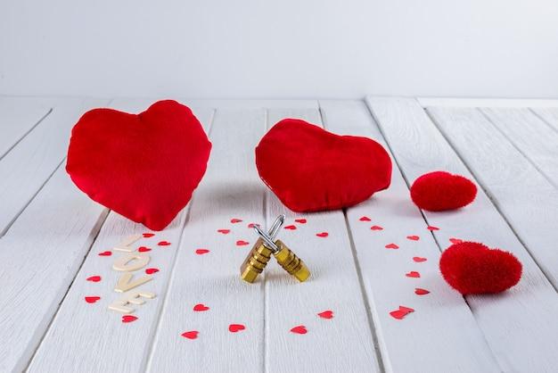 Valentinsgrußhintergrund mit roter herzform und paar-kombinationsvorhängeschloß auf weißem holztisch