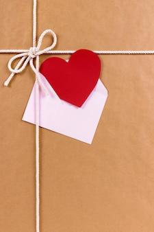 Valentinsgrußkarte auf einem braunen papierpaket oder einem geschenk gebunden mit schnur.